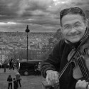 Alain Mather plays for a few Euros a day on the steps of the bascillica Sacre Coeur overlooking the city of Paris, France.